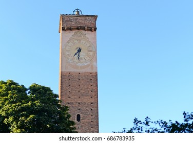 medieval clock tower against blue sky in pavia, italy, europe