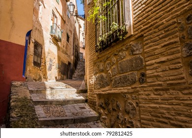 Medieval cobbled and stepped street with flowery balconies and public lighting lamps in the city of Toledo. Spain