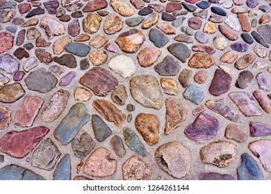 Medieval cobbles asphalt. Stone pavement texture. Cobblestone pavement. Cobble texture - stones in the golden sand.