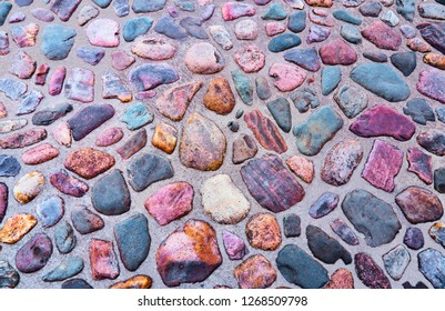 Medieval cobbles asphalt. Stone pavement texture. Cobblestone pavement. Cobble texture - stones in the beige sand.