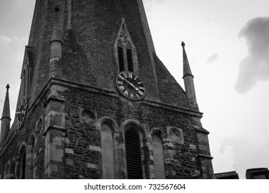 Medieval English Church. All Saint's Leighton Buzzard, England. Photograph of the main steeple with clock face. Black and white filter added in post-production. Taken summer 2017