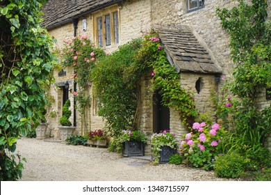 Medieval entrance with green plants and flowers to old stone house - Cotswolds, UK