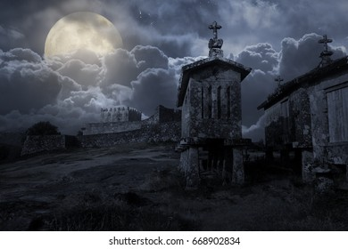 Medieval european castle in a cloudy full moon night with old and weathered granite granaries in the foreground