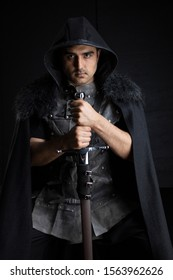 Medieval or fantasy male character in leather jerkin and cloak with weapons