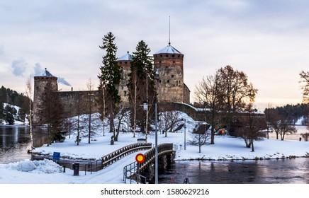 Medieval fortress Olavinlinna on Saimaa lake on a cloudy winter day. Savonlinna, Finland.