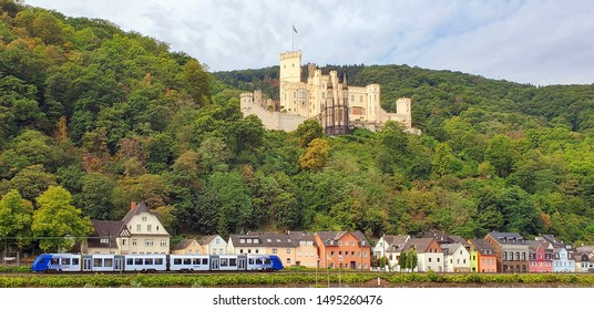 medieval German castle on mountain side with row of colorful village homes and train