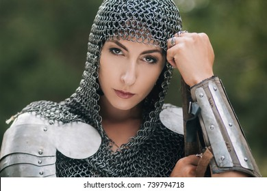 Medieval girl warrior, in a chain mail hood with a sword in his hand. A woman in European armor. Viking. Fantasy
