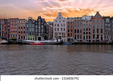 Medieval houses along the river Amstel in Amsterdam Netherlands at sunset