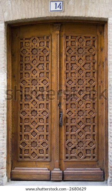 Medieval intricately carved door on a building in Toledo, Spain.  With street number.
