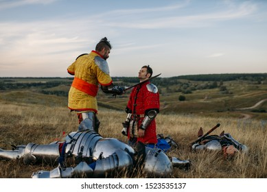 Medieval knight in armor prepares to cut off head