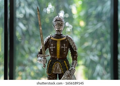 Medieval Knight Gothic Plate Armour with sword on green bokeh background.