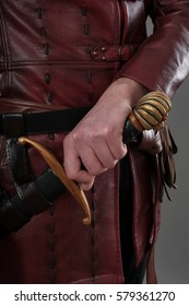 Medieval knight holding hand on his sword. Closeup. Studio shoot