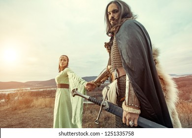 Medieval knight with lady on the sunset background.
