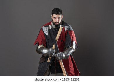 Medieval knight on grey background. Portrait of brutal dirty face warrior with chain mail armour red and black clothes and battle axe.