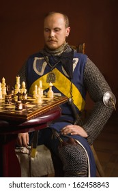 Medieval knight plays chess in a castle