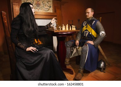 Medieval knight plays chess with death in a castle
