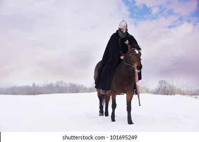 Medieval knight of St. John (Hospitallers) on a bay horses