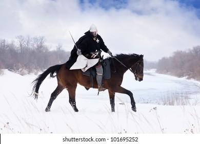 Medieval knight of St. John (Hospitallers) riding on a bay horse