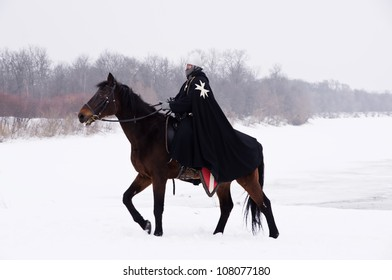 Medieval knight of St. John (Hospitallers) on a bay horse