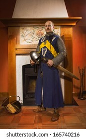 Medieval knight with sword against fireplace