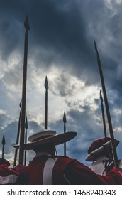 Medieval knights holding spear, warriors ready for battle. Red and white uniforms. Dramatic sky before storm. Fight, army concept, conceptual. History, historical background. Knight attack, chivalry