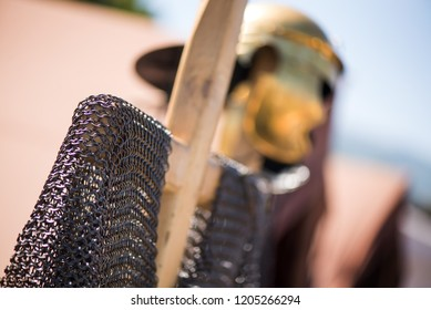 Medieval knight's iron chain armor on wooden cross hanger. Golden helmet in background. reenactment festival in summer. Preparing for fight and battle. Weapons, shields, armor ready