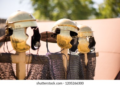 Medieval knight's iron chain armor and golden helmets on wooden cross hanger in a row. Reenactment festival in summer. Preparing for fight and battle. Weapons, shields, armor ready