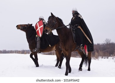 Medieval knights of St. John (Hospitallers) on a bay horses