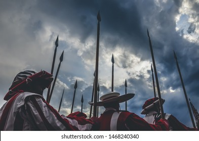 Medieval knights warriors holding spear ready for battle. Red and white uniforms. Photographed with dramatic sky before storm. Fight, army concept, conceptual. History, historical background