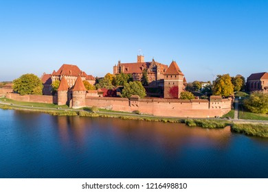 Medieval Malbork (Marienburg) Castle in Poland, main fortress of the Teutonic Knights at the Nogat river. Aerial view in fall in sunset light.