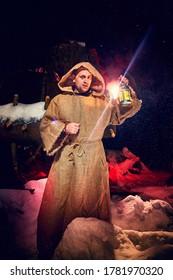 Mittelalterlicher Mönch in Leinwand mit Lattern im dunklen Wald mit Schnee und rotem Licht in der Winternacht. Fantasie- oder Märchen über wandernden Mönch. Geschichte über die Kräfte des Guten und Bösen in der Welt