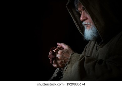 Medieval monk prays with rosary