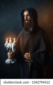 Medieval monk in robe holds a candlestick in hands