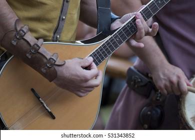 Medieval musician plays an classic guitar on a fair.