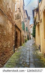 Medieval narrow street in old city Siena, Tuscany, Italy.