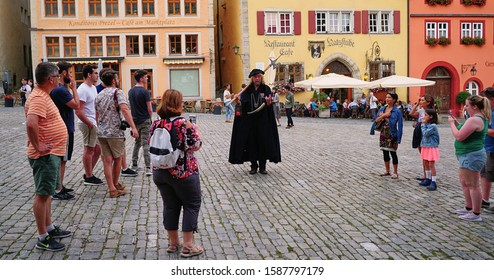 The medieval night watchman dressed in black cape and carrying his long pole axe walks the cobblestone square while tourists watch in Rothenburg, Germany. August 2019.