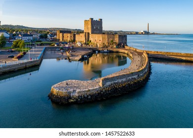 Medieval Norman Castle and harbor in Carrickfergus near Belfast, Northern Ireland, UK. Aerial view  in sunset light. Old power plant in the background