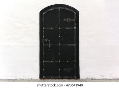 Medieval old black door with metal decoration on white wall