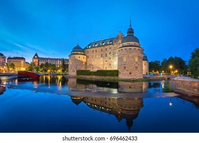 Medieval Orebro Castle reflecting in water in the evening, Orebro, Sweden