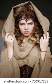 Medieval outfit of the princess, sorceress, witch with a hood and a tiara on her head. Portrait of a beautiful teenage girl, women. Green eyes. Serious View