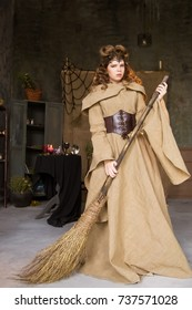Medieval outfit of a princess, a sorceress, a witch with a hood and a tiara on her head. Beautiful girl teenager, women. holding a broom, cleaning the house. Flying on a broom