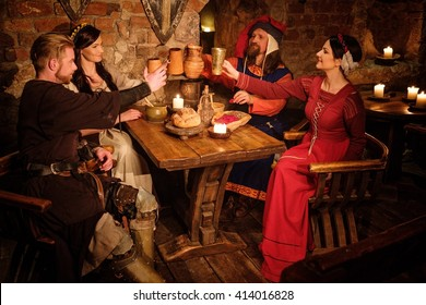 Medieval people eat and drink in ancient castle tavern.