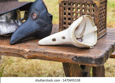 Medieval plague leather masks, knight's helmet, hat, transparent chest on a wooden table. Carnival concept.