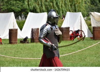 Medieval Polish knight with a sabre preparing to fight. Historical reenactment in Brodnowski park in Warsaw, Poland
