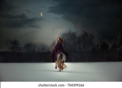 Medieval Queen on white horse at twilight winter forest