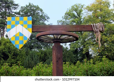 Medieval quintain with shield on a revolving post used for jousting practice.