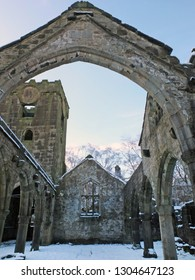 the medieval ruined church in heptonstall covered in snow showing arches and columns against a blue winter sky