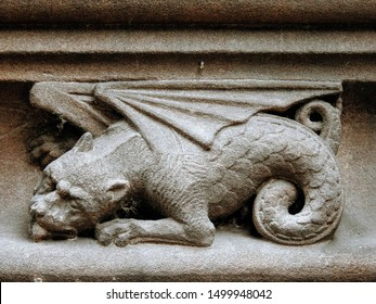 Medieval sandstone ornament depicting a dragon with curled up tail, carved into a decorative frieze on the upper part of the Chester Cathedral facade. City of Chester, Cheshire, England