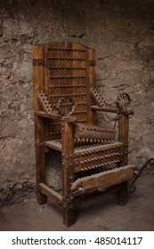 Medieval spiked torture armchair in dark room