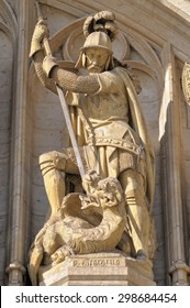 Medieval statue of Archangel Michael killing a devil on entry arch to City Hall on Grand Place in Brussels.
